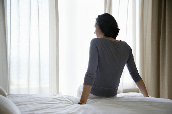 Kvinde kigger ud af vinduet mellem gardiner