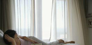 Læsning-i-sengen-med-gardinerne-for