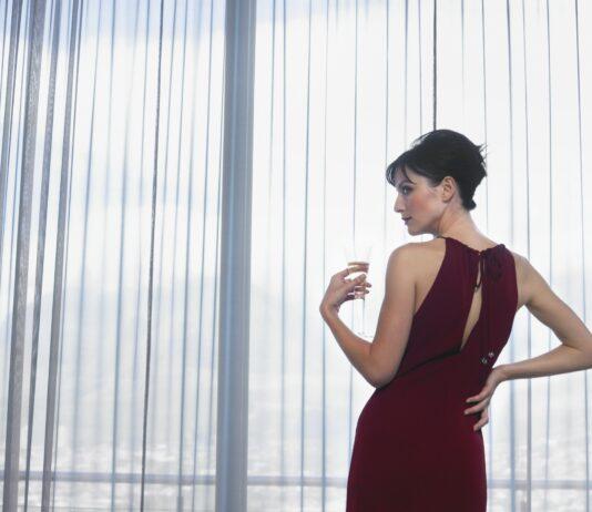 Velklædt kvinde står ved vindue og gardiner